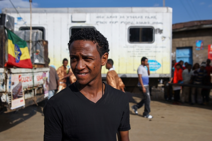 Samson standing in front of a mobile HIV-testing clinic. Photo credit: duckrabbit / International HIV/AIDS Alliance.